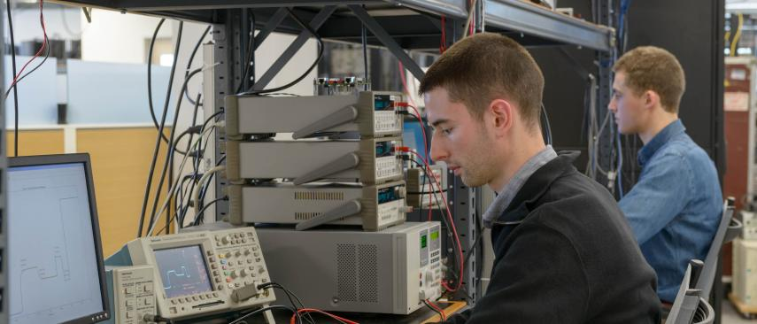 Test technicians using oscilloscopes
