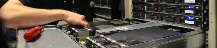 person adding computer equipment to an open drawer in a server rack